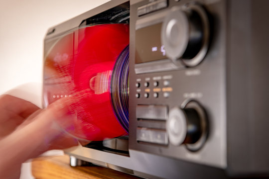 A red colored CD is placed into its player