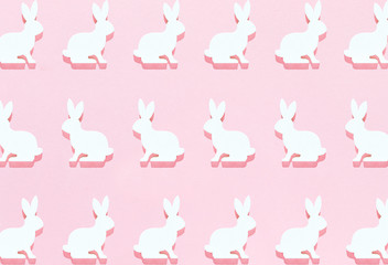 Easter white bunny flat lay pattern on bright pink background with hard shadows, wallpaper, greeting card, top view.