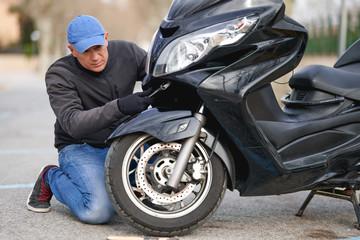 mechanic repairing motorcycle at street