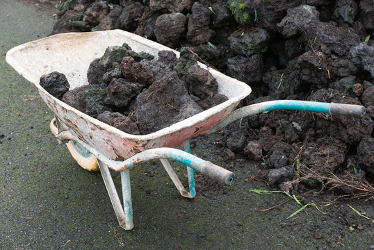 Old painted wheelbarrow with soil and rocks