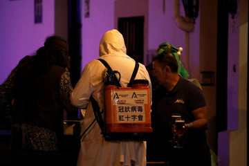 A carnival reveller dressed up as a health worker spraying disinfectant in a protective suit to avoid contracting coronavirus, stands next to a waiter serving beers outside a restaurant during the carnival in Ronda
