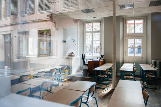 View from the street of large school classroom with empty seats - reflections of city in the window