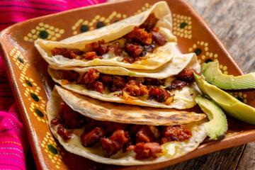 Mexican quesadillas with chorizo on wooden background