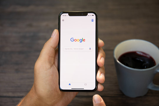 Man holding iPhone X with social networking service Google