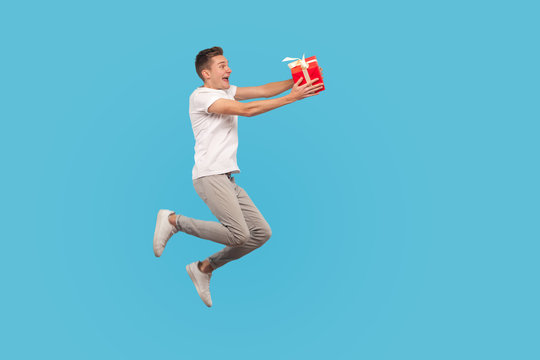Full length lucky overjoyed man in casual outfit running in air with gift box and laughing, jumping holding present with expression of extreme happiness. indoor studio shot isolated on blue background
