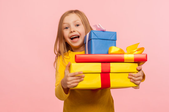 Delighted amazed little girl embracing lot of gift boxes, looking at camera with surprise and sincere childish happiness, shocked by many birthday presents. indoor studio shot, pink background