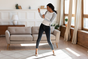 Overjoyed african American woman dancing alone at home