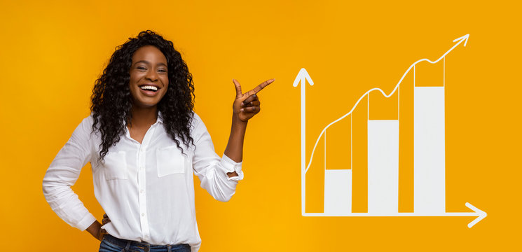 Happy African American woman pointing aside at business graph