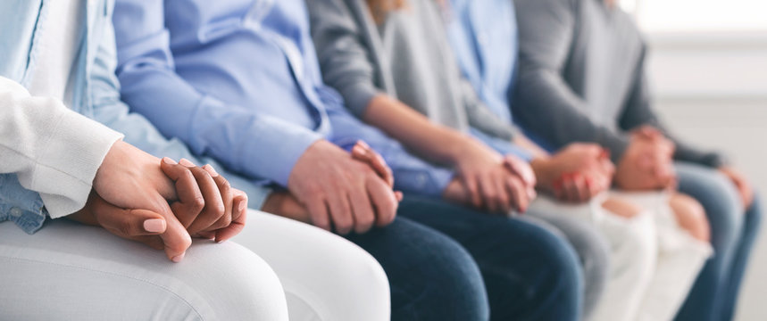 Unrecognizable people sitting in row and holding hands during therapy session