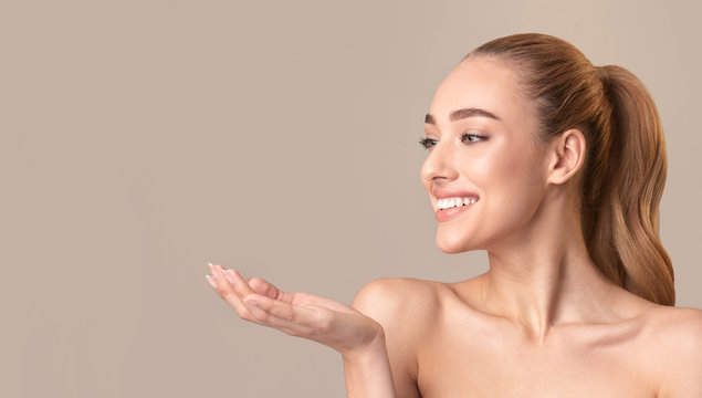 Woman Posing Holding Invisible Object On Hand Over Beige Background