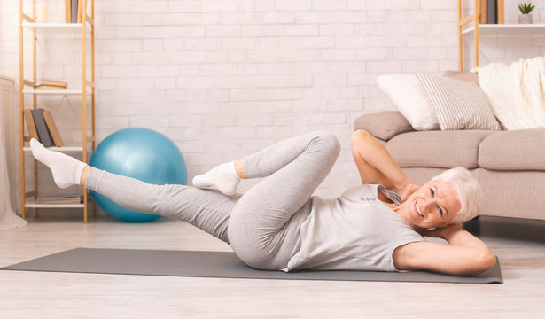 Sporty senior woman doing abs exercise on floor at home