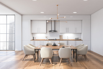 Panoramic white kitchen interior with table