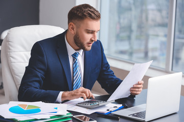 Obraz Male accountant working in office - fototapety do salonu