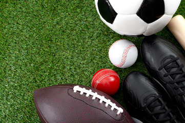 Competitive match and team sports concept with soccer, cricket and american football balls black cleats or sport boots and wooden baseball bat isolated on green grass with copy space