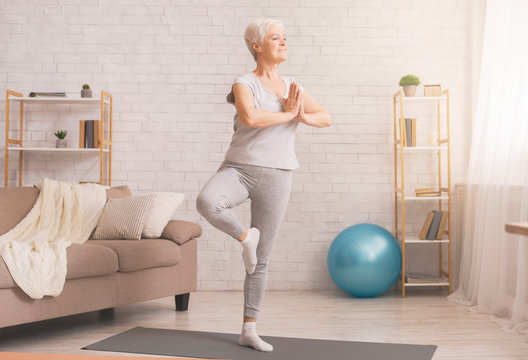 Senior woman doing yoga tree pose at home, free space