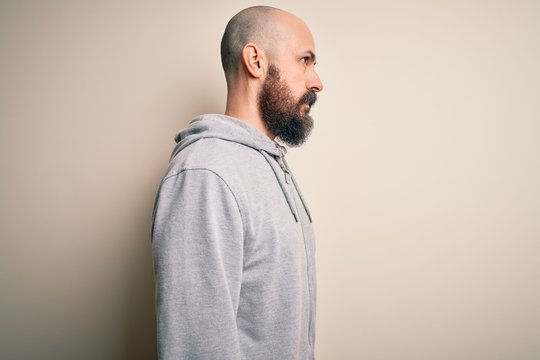 Handsome sporty bald man with beard wearing sweatshirt standing over pink background looking to side, relax profile pose with natural face with confident smile.