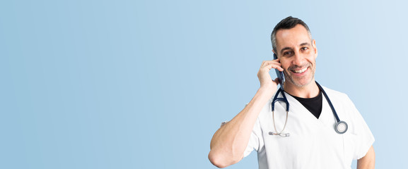 Handsome middle aged male doctor wearing white coat is happy talking on the phone in front of blue wall