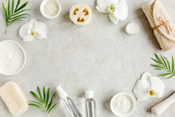 Foto op Plexiglas Spa Spa treatment concept. Natural/Organic spa cosmetics products, sea salt, massage brush, tropic palm leaves on gray marble table from above. Spa background with a space for a text, flat lay, top view
