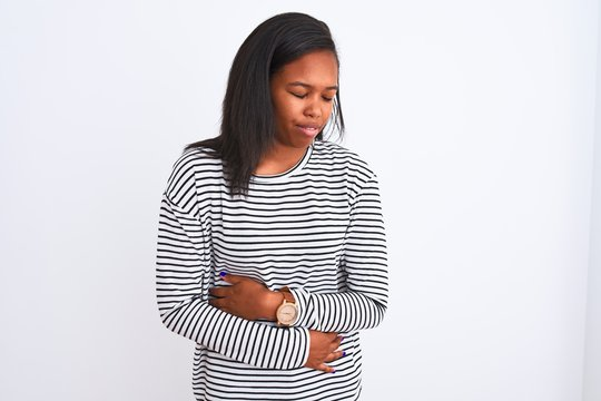 Beautiful young african american woman wearing winter sweater over isolated background with hand on stomach because indigestion, painful illness feeling unwell. Ache concept.