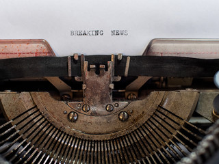 close-up text BREAKING NEWS. old vintage typewriter with a sheet of white paper