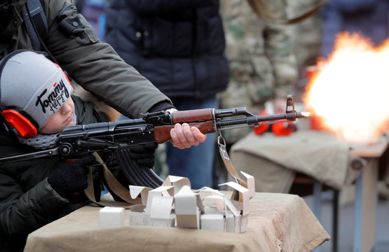 Boy shoots with a machine gun at the base of the Belarusian Interior Ministry's special forces unit during celebrations of Maslenitsa, or Pancake Week