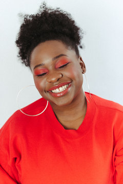 close-up portrait of smiling young black woman wearing orange eye make-up and red sweater