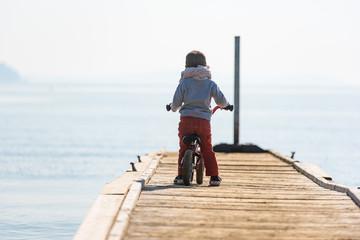 Enfant seul en vélo sur un ponton