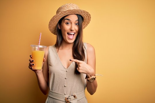 Young beautiful woman on vacation wearing summer hat drinking healthy orange juice very happy pointing with hand and finger
