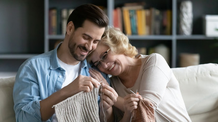 Smiling mature mom and adult son knitting together