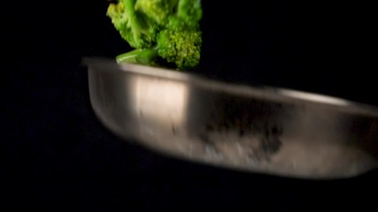 Fotobehang - cooking vegetable in pan, broccoli and carrot , slow motion