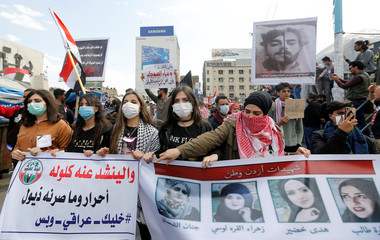 University students girls carry pictures of demonstrators who were killed during ongoing anti-government protests in Baghdad