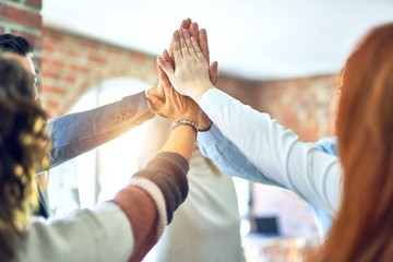 Fototapeta Group of business workers standing with hands together highing five at the office obraz