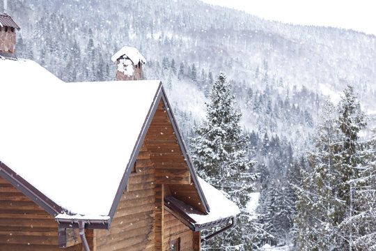 Wooden cottage with snowy roof. Winter vacation