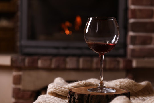 Glass of wine near fireplace indoors. Space for text