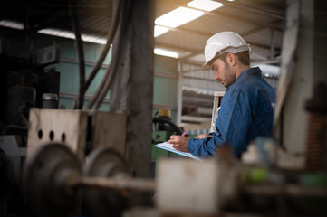 Factory technicians are surveying machines and recording inspection details and writing reports for submission to management. They wear uniforms, safety helmets, and protective goggles.