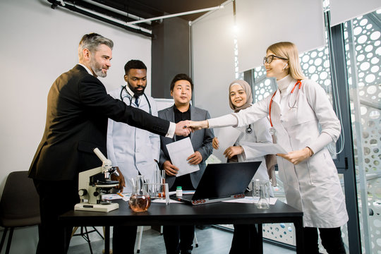 Team of doctors, scientists, pharmaceutical workers having meeting in modern lab with equipment. Caucasian man and woman shaking hands, after successful cooperation and results