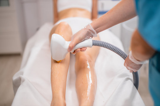 close-up photo of female legs on laser epilation procedure. slim woman came to get epilation with ipl machine. special ointment applied on legs