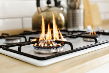 Keuken foto achterwand Vuur Macro closeup of modern luxury gas stove top with blue fire flame knobs bokeh blurry blurred background