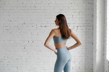 Sporty girl in fitness clothes against a white brick wall