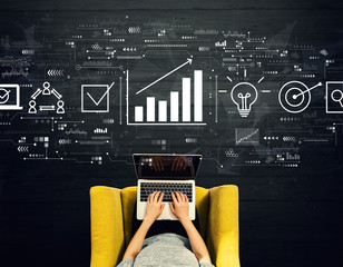 Wall Mural - Marketing concept with person using a laptop in a chair