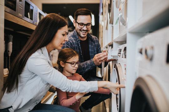 Happy family buying washing machine in store.