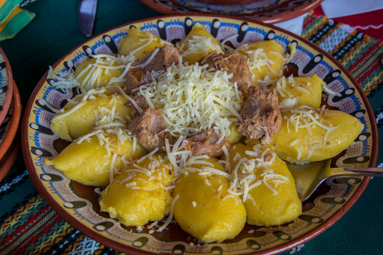 Natural food, hominy or mamaliga on a plate with grated cheese on top, traditional bulgarian meal
