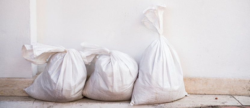 three white plastic garbage bags on the street. Against white wall