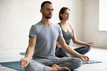 People meditating sitting on mats, focus on male instructor