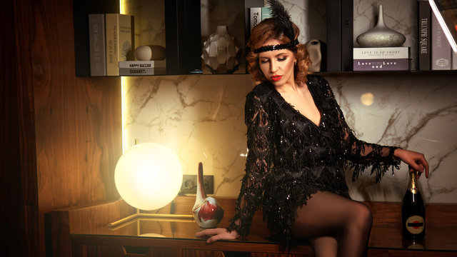1920s retro style. Beautiful young woman in a dress and a fur cape poses in a chic interior, drinks champagne and laughs. The photo shows soft noise for vintage styling. Color photo.