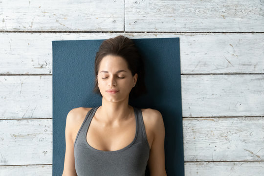 Above view young woman lying on mat during Shavasana pose