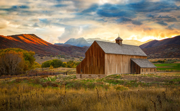 Autumn sunset above a classic old barn in rural Utah, USA.