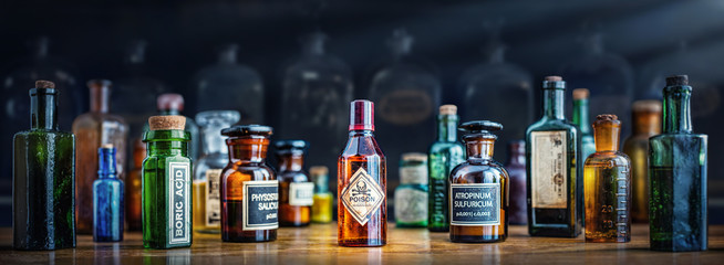 Foto op Canvas Apotheek A bottle of poison on a background of old medical, chemistry and pharmacy glass. Chemistry and pharmacy history panoramic concept background. Retro style.