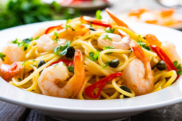 Pasta with prawns and vegetables on wooden background