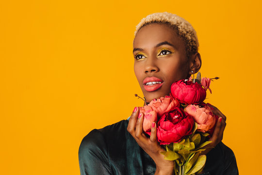 Portrait of a beautiful young woman holding bouquet of red peony flowers with trendy fresh makeup of orange lips and yellow eyeshadow